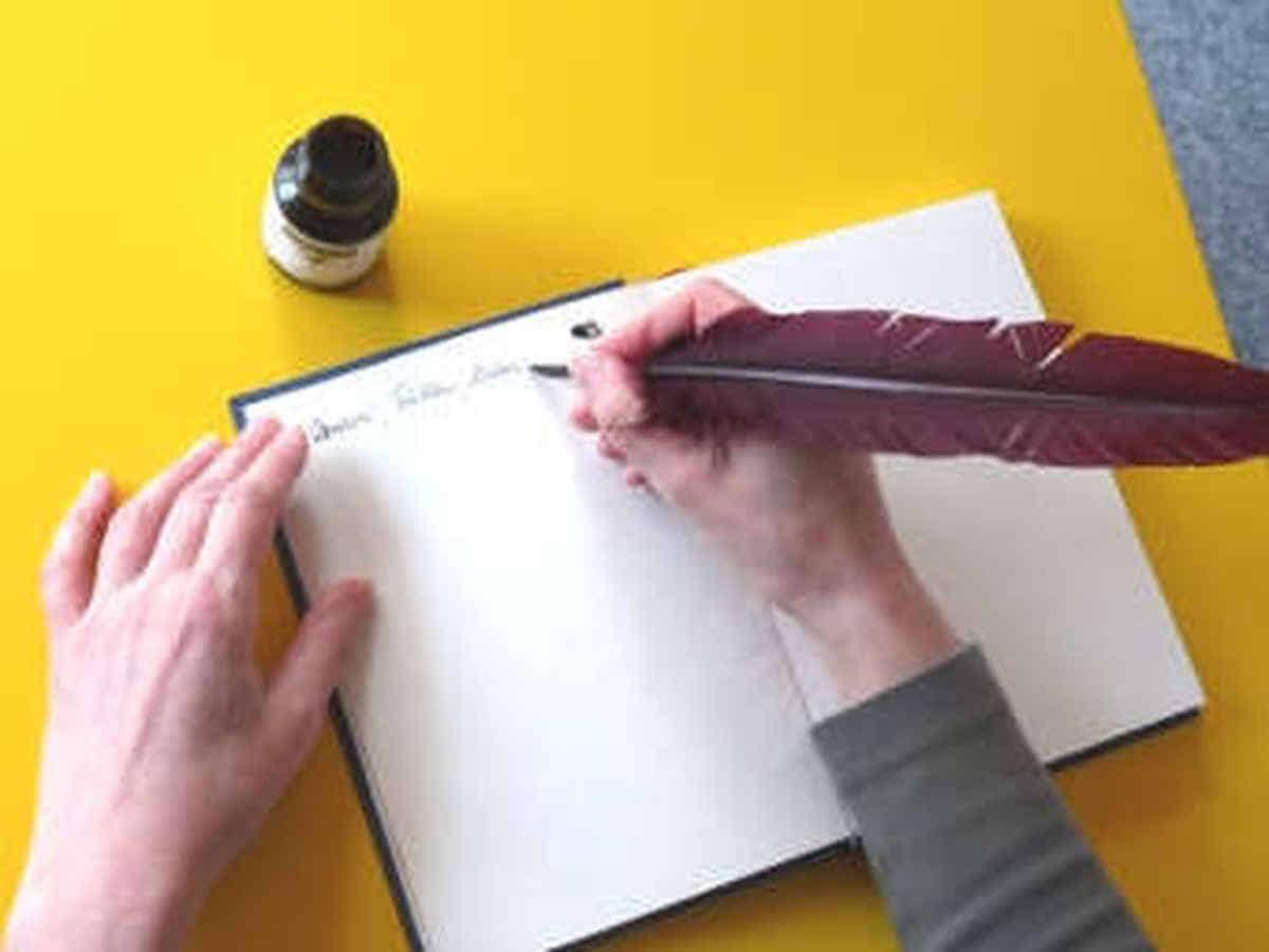 Foto: Hier schreibe ich mit Feder und Tinte einen Text auf ein Papier.