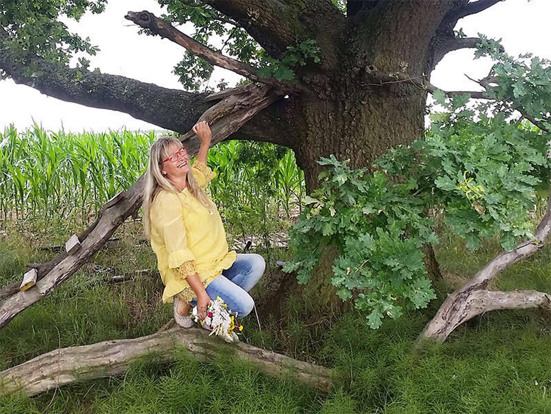Foto: Brigitte hockt mit einem Blumenstrauß in der Hand auf einem Ast unter einer uralten Eiche.
