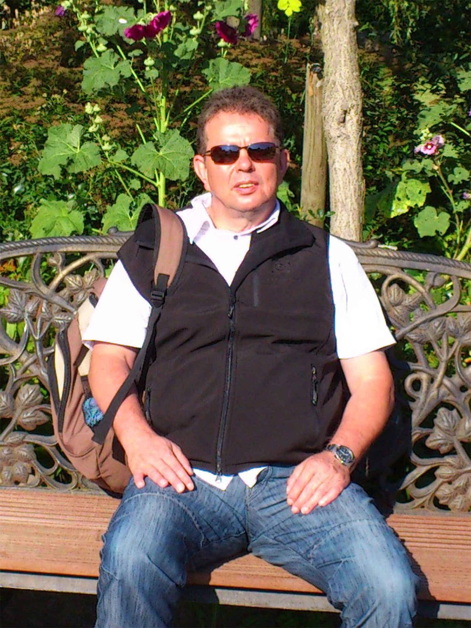 Foto: Joachim sitzt auf einer Parkbank in der Sonne.