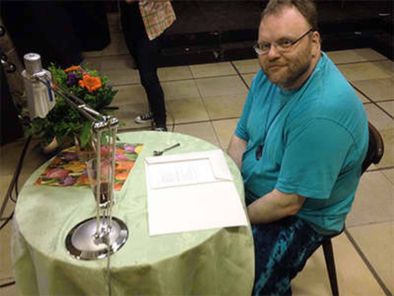 Foto: Ich sitze in der Pause an meinem Lesetisch mit Blumenstrauß.