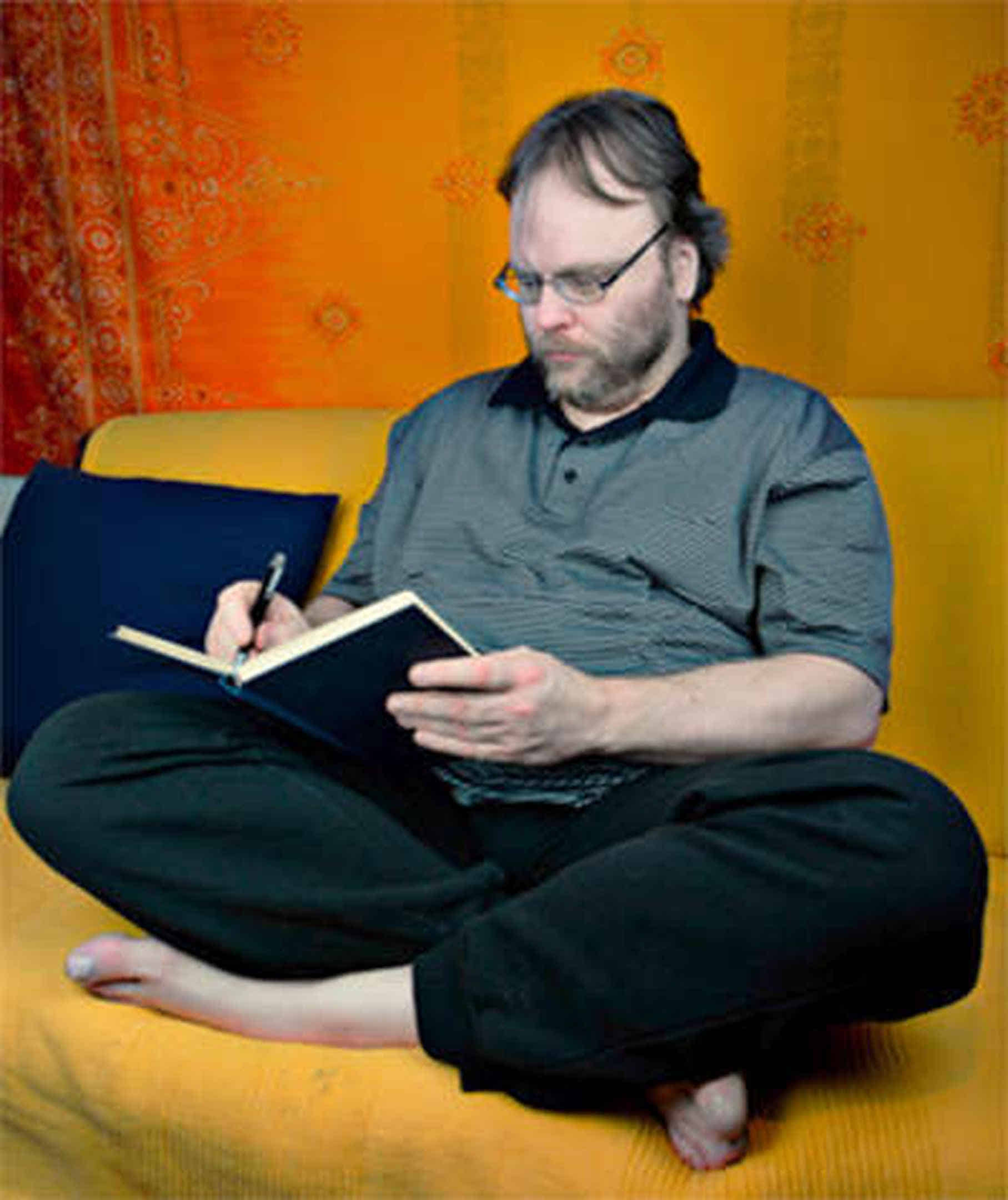 Foto: Ich sitze im Schneidersitz auf meinem Sofa und schreibe einen Text in ein Buch.
